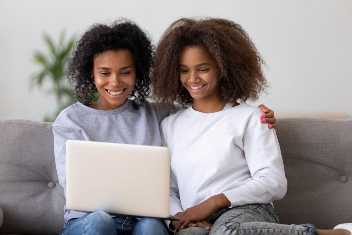 Mother and daughter look at daughter's school work on a digital portfolio