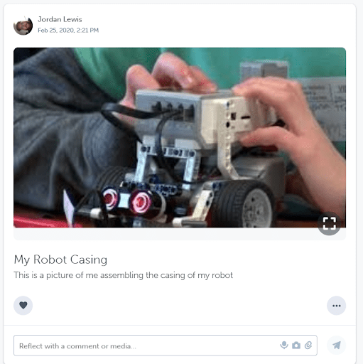 A student showcasing their work on a robot