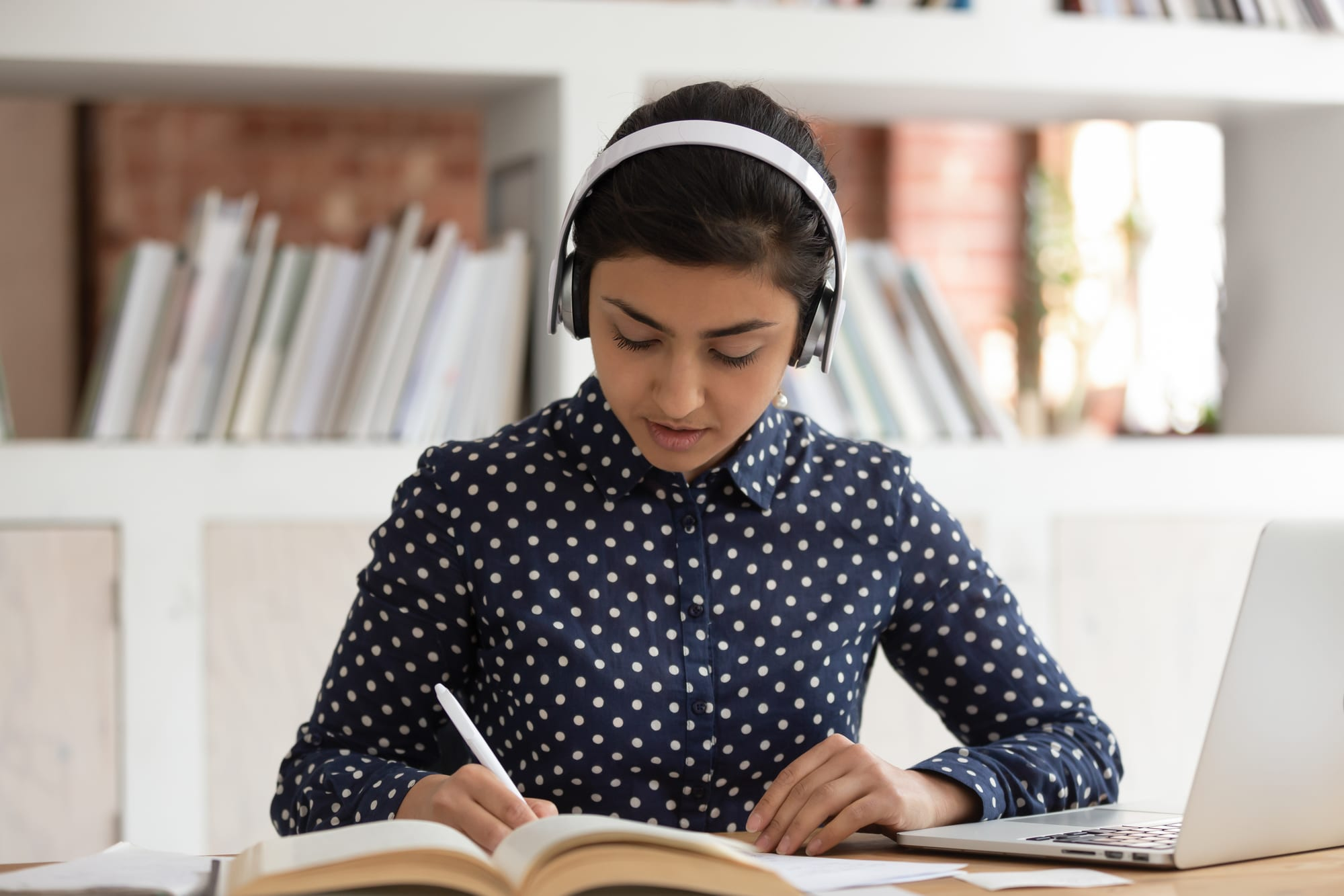 A female student is focusing on her school work and wearing headphones