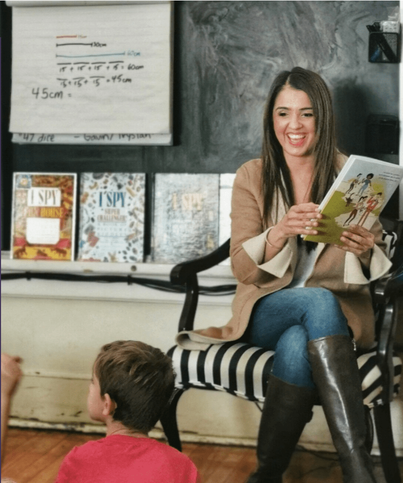 educator reads at the head of the classroom