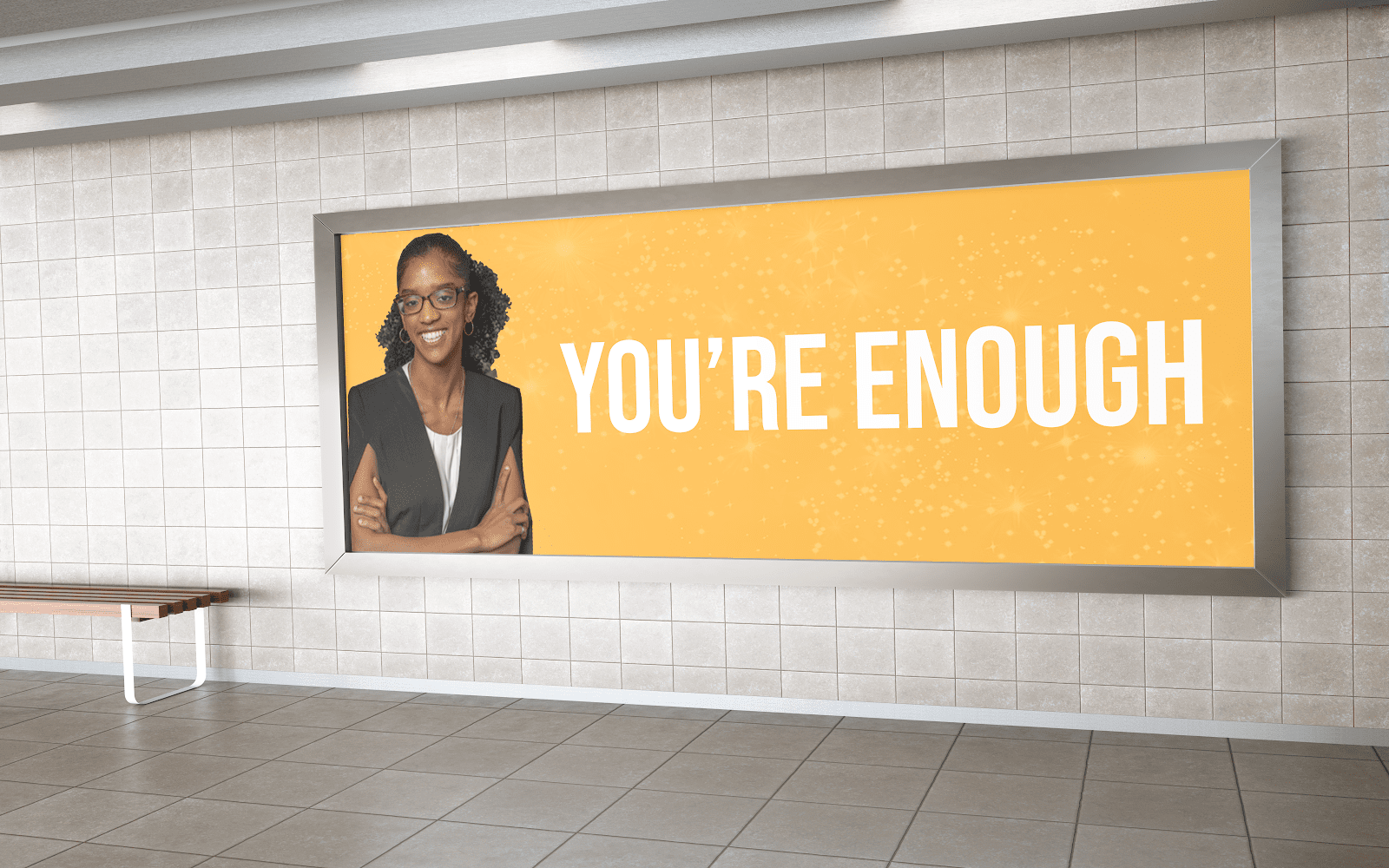 """A billboard with a photo of Janelle and the quote """"You're enough."""""""